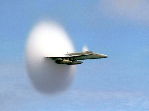 A cloud forms as this F/A-18 Hornet aircraft speeds up to supersonic speed. Aircraft flying this fast push air up to the very limits of its speed, forming what's called a bow shock in front of them. Similar bow shocks are also found in a variety of forms in space, and new research suggests they may contribute to heating of the material around them. Credit: Ensign John Gay, USS Constellation, U.S. Navy