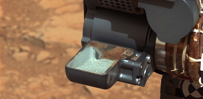 his image from NASA's Curiosity rover shows the first sample of powdered rock extracted by the rover's drill. Image credit: NASA/JPL-Caltech/MSSS
