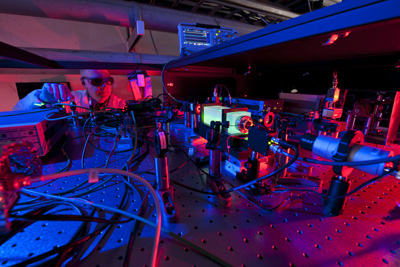A Fermilab scientist works on the laser beams at the heart of the Holometer experiment. The Holometer will use twin laser interferometers to test whether the universe is a 2-D hologram. Credit: Fermilab