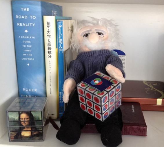 Figure of Albert Einstein, the smile of Mona Lisa and Qbe: Quark Matter on Rubik's 3x3 Cube, next to the Road to Reality: A Complete Guide to the Laws of the Universe. Photo courtesy of prof. T. Kodama, Rio de Janeiro, Brazil.